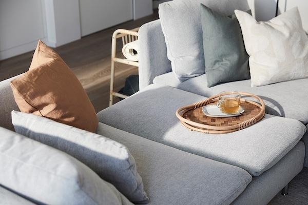 Un plateau en rotin est posé sur un canapé gris clair.