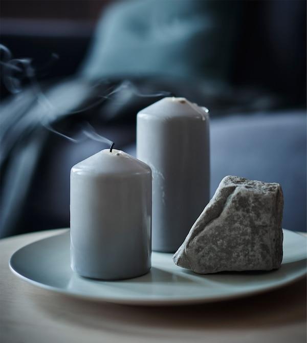 Un plato con dos velas gruesas y una roca.