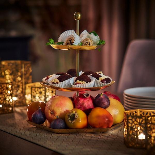 un présentoir à étages posé sur une table avec des fruits et des gourmandises