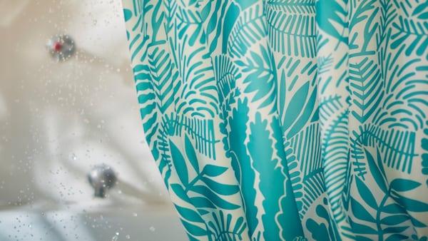 Un prim-plan cu perdeaua de duș GATKAMOMILL cu un imprimeu jucăuș cu frunze în nuanțe de turcoaz și alb lângă o baie.
