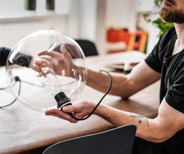 Un primer plano de un hombre sentado junto a una mesa mientras sostiene una gran lámpara de mesa de vidrio.