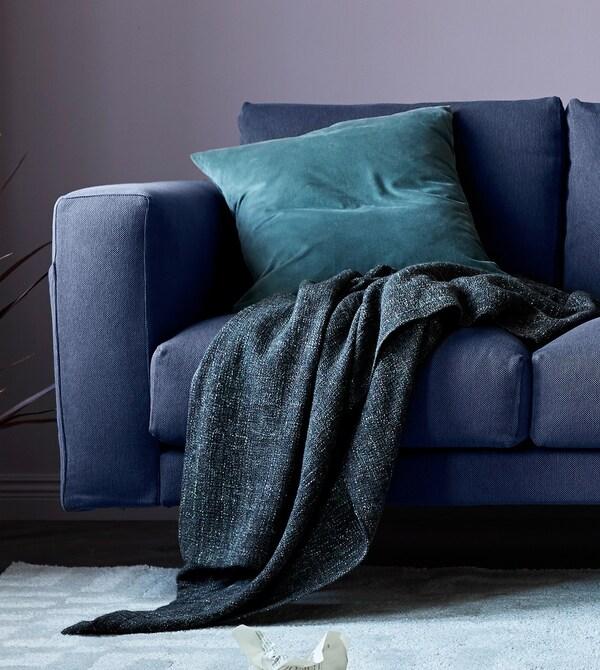 Un primer plano de un sofá gris con una manta y un cojín.