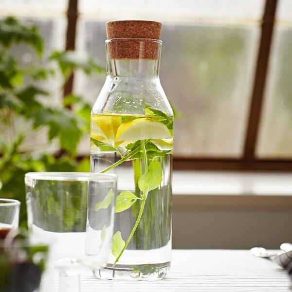 Un primer plano de una jarra sobre una mesa que contiene rodajas de limón y menta.