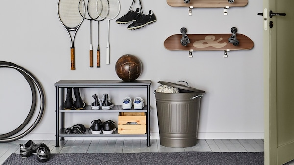 Un range-chaussures PINNIG avec des chaussures et un ballon de soccer dans un bac KNODD avec un couvercle ouvert. Des raquettes et des planches à roulettes sont accrochées au mur au-dessus.