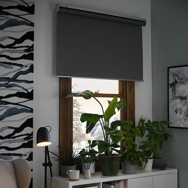 Un rebord de fenêtre avec plusieurs plantes en pot, devant une fenêtre avec des stores intelligents gris partiellement ouverts.