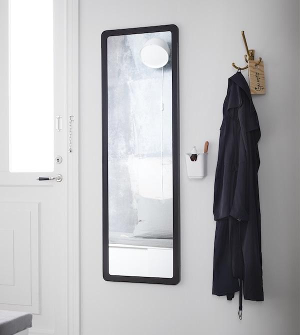 Un recibidor blanco junto a la puerta de entrada. Un espejo con marco largo negro y un abrigo negro en un gancho de pared.