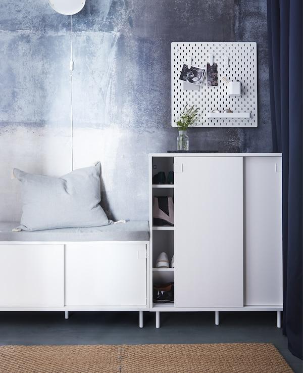Un recibidor con un banco MACKAPÄR blanco que también tiene compartimentos de almacenaje. Un armario blanco que muestra zapatos.