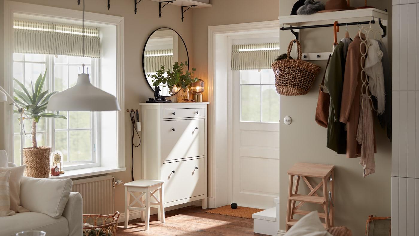 Un recibidor pequeño con una puerta blanca, un zapatero blanco, un espejo redondo y un perchero/estante blanco con chaquetas y un paraguas.