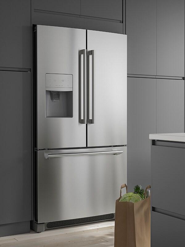 Un réfrigérateur à deux portes STJÄRNSTATUS en acier inoxydable dans une cuisine grise.