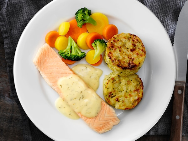 Un repas de saumon avec grains nordiques et légumes cuits à la vapeur dans une assiette blanche. Autour de l'assiette se trouvent des couverts argentés, un verre à eau transparent et une serviette grise.