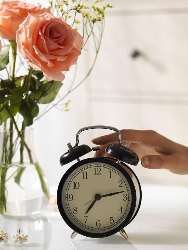 Un réveil DEKAD noir. Il y a un vase contenant des roses couleur pêche en arrière-plan.
