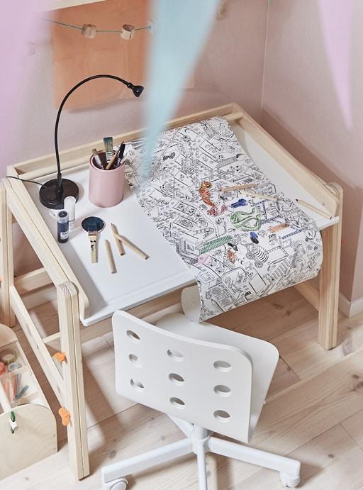 Un rollo de papel para colorear en el escritorio de un niño o niña con una silla blanca contra una pared rosa.