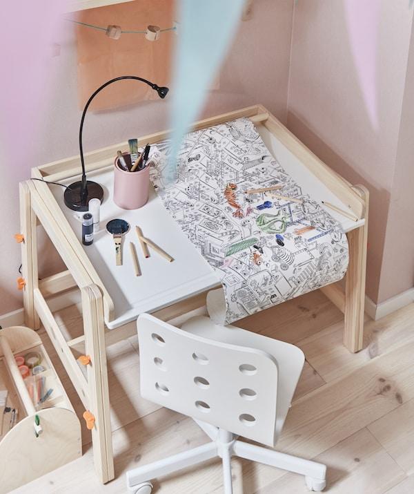 Un rouleau de papier à colorier sur un bureau d'enfant avec une chaise blanche contre un mur rose.