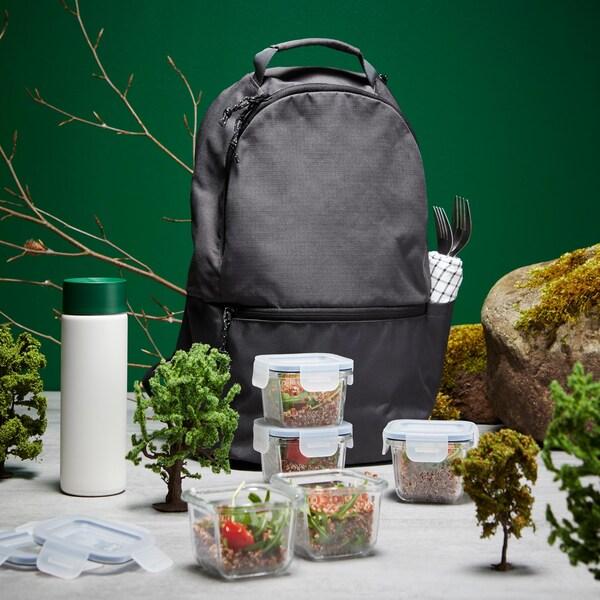 Un sac à dos gris, un assortiment de contenants pour aliments et une bouteille isotherme.