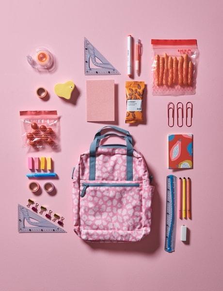 Un sac à dos rose à motifs sur un sol rose. Autour de lui sont disposés divers effets scolaires, tels que des stylos et des trombones.