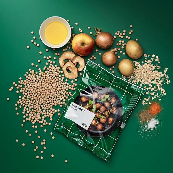 Un sac de boulettes végétales HUVUDROLL entouré des ingrédients, y compris des pommes, des pommes de terre, de l'avoine et des oignons.