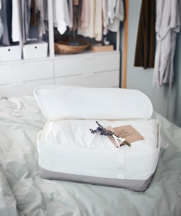 Un sac de rangement posé sur un lit contenant une couette épaisse avec dessus une jolie note manuscrite et quelques brins de lavande.