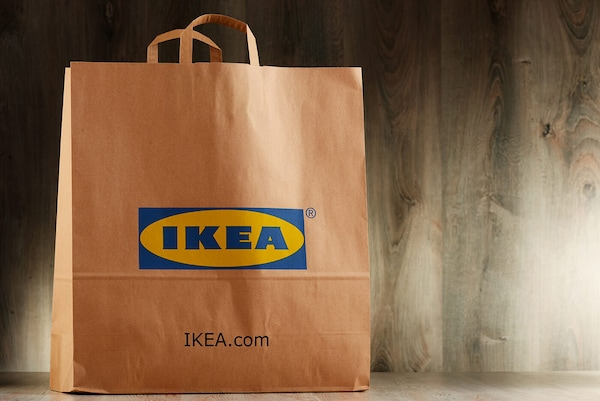 Un sac en papier avec le logo IKEA imprimé sur le côté et les mots IKEA.com