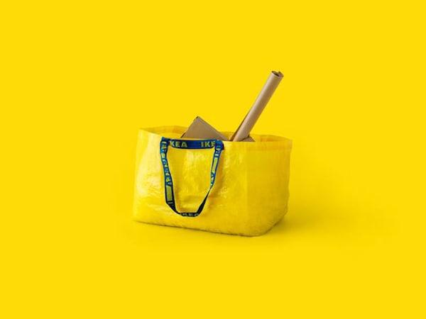 Un sac IKEA jaune vif contenant du papier kraft et des boîtes marron.