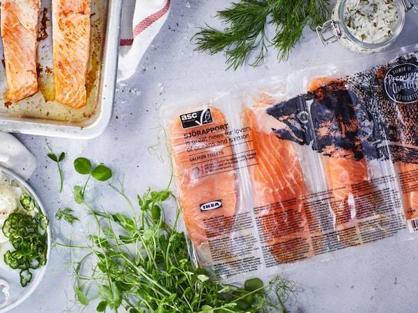 Un sac non ouvert de filets de saumon SJÖRAPPORT repose sur le comptoir. Il y a des filets cuits à côté.