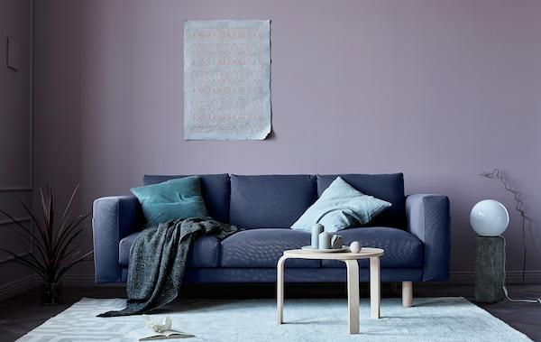 Un salón actualizado para el otoño tiene un sofá gris, paredes rosa, cojines y elementos naturales, como piedras.