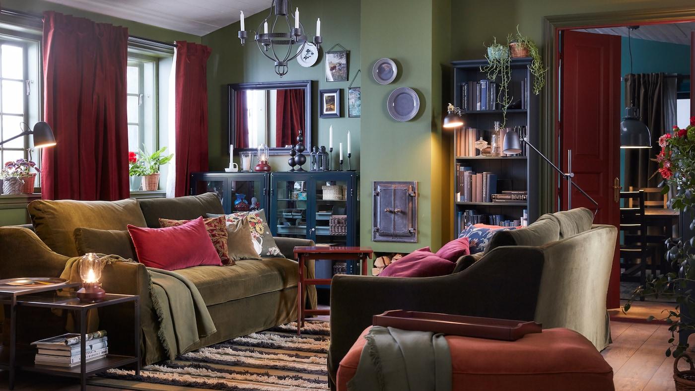 Un salon avec deux canapés vert olive, un repose-pieds rouge clair, un chandelier noir, des rideaux rouges-bruns et un tapis rayé.