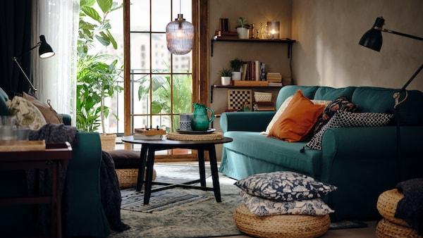 Un salon avec un canapé-lit trois places turquoise foncé VRETSTORP, un tabouret ALSEDA en fibres de bananier et une table basse KRAGSTA.