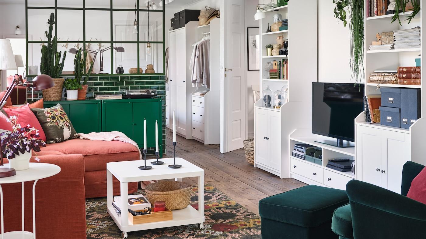 Un salon avec un fauteuil à oreilles et un repose-pieds en vert foncé, des armoires vertes et une combinaison de rangement TV HAUGA.