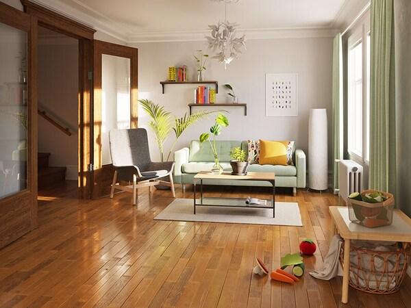 Un salon avec un plancher brillant, un canapé vert clair, un fauteuil gris, et des accessoires et jouets colorés.
