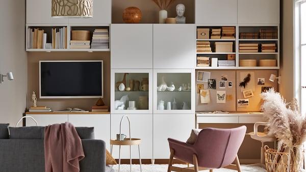 Un salon avec un rangement modulaire BESTÅ blanc couvrant un mur, des rangements ouverts et fermés, un canapé, une télévision et un poste de travail.