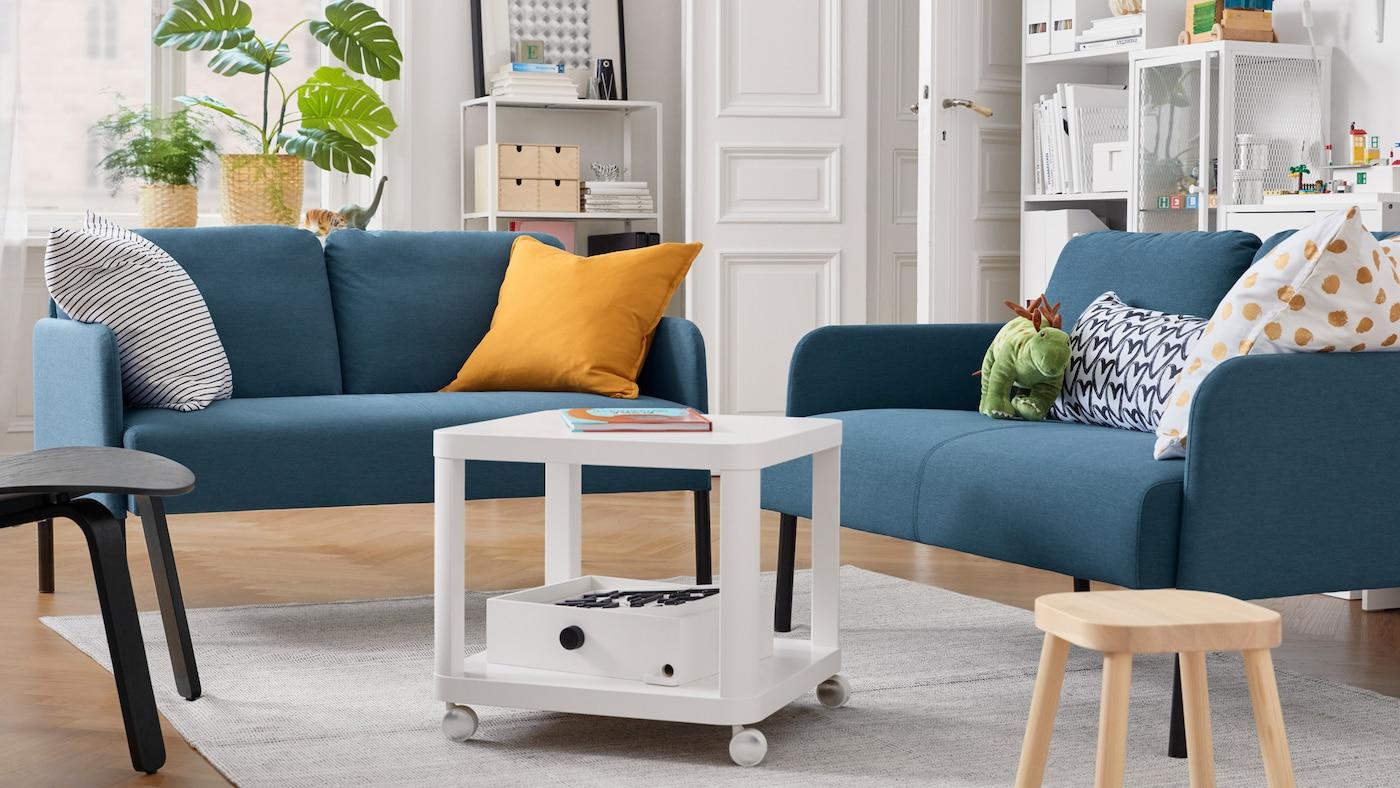 Un salón con dos sofás de dos plazas, una mesa auxiliar blanca con ruedas, un taburete infantil, cojines y plantas en macetas.