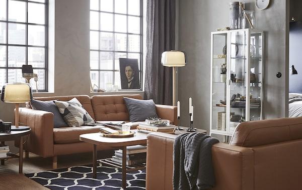 Un salón con dos sofás de piel marrón, una mesa de centro, una vitrina y lámparas.