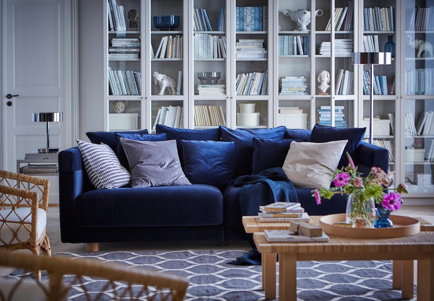 Un salón con estilo escandinavo moderno de IKEA con un sofá azul oscuro, una librería blanca al fondo y una mesa y sillas de maderas claras con una lámparas en metal.