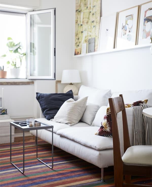 Un salón con paredes blancas, un sofá blanco y una alfombra con dibujos coloridos.
