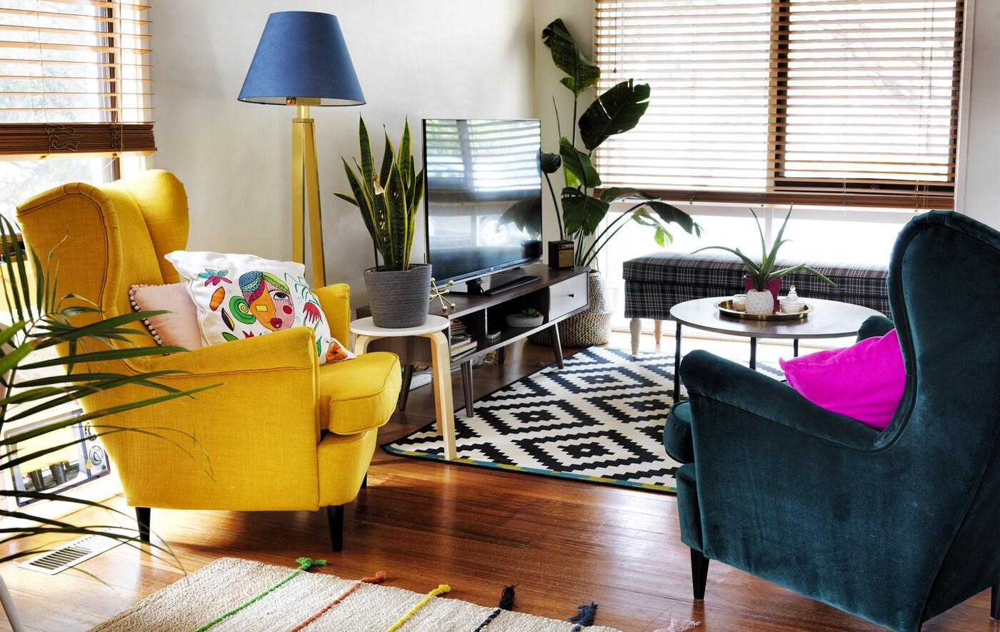 Un salón con sillones orejeros en amarillo y verde oscuro, una alfombra negra y blanca y un mueble de TV.
