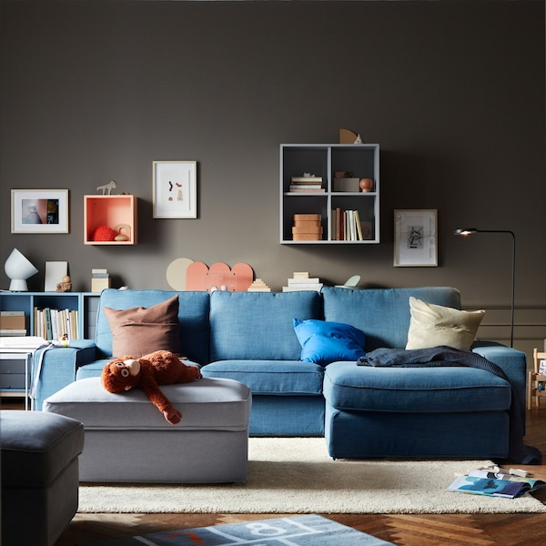 Un salón con un sofá azul, un reposapiés gris y armarios IKEA EKET en la pared.