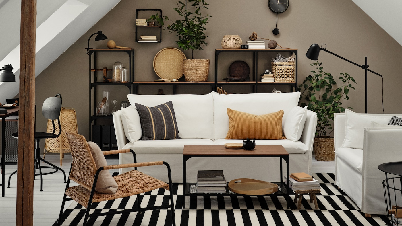 Un salón con un sofá blanco de tres plazas y un sillón ancho de una plaza, una alfombra plana y muebles de la serie FJÄLLBO.