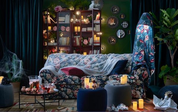 Un salon décoré pour l'Halloween meublé d'un canapé fleuri et d'une bibliothèque illuminée par des guirlandes. Des décorations et des bougies participent à l'ambiance générale de la pièce.