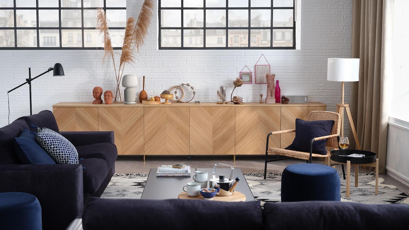 Un salón elegante con un sofá de 3 plazas, un sofá cama de 2plazas, una combinación de almacenaje con puertas y un sillón.