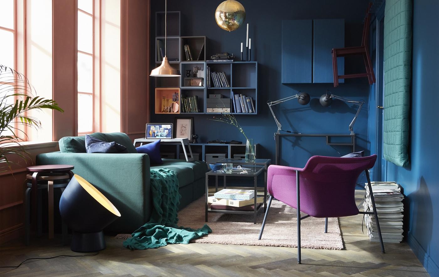 Un salón flexible y cómodo que utiliza un moderno tono de azul en la pared con un sofá verde y textiles y un suelo de madera.