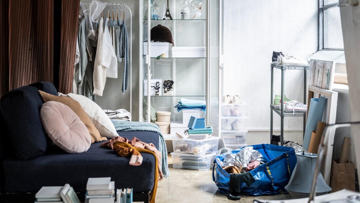Un salon légèrement désordonné avec un canapé bleu, une étagère à chaussures, quelques boîtes de rangement empilables et un sac FRAKTA à moitié plein.