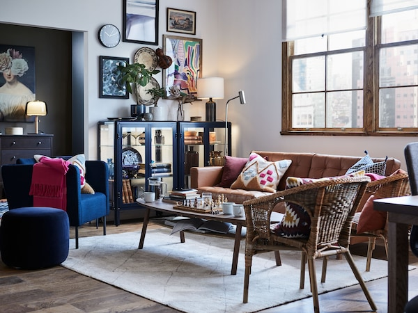 Un salon meublé de fauteuils et d'un canapé LANDSKRONA disposés autour d'une table basse, et une vitrine à gauche du canapé.