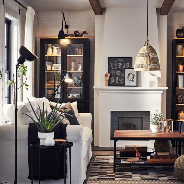 Un salon où se trouvent un canapé blanc, des lampes, une table d'appoint noire, un tapis à motifs beiges et deux tables basses au fini noir et bois.