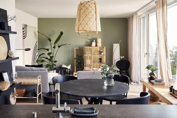 Un salon ouvert et une salle à manger décorés d'un style appaisant avec des meubles en bambou et en rotin.
