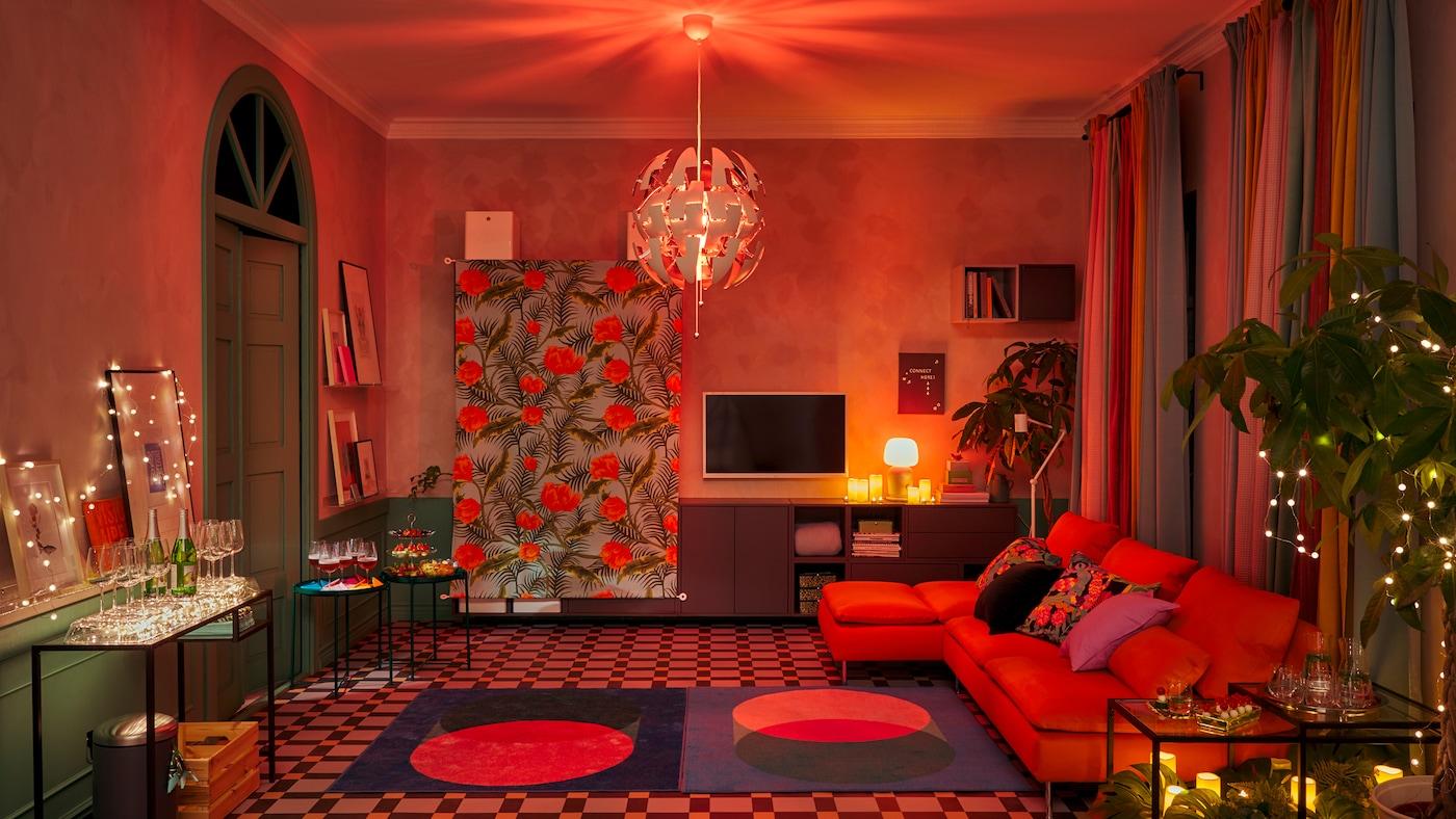 Un salon préparé pour une fête avec des meubles le long des murs, une piste de danse spacieuse ainsi que des décorations et un éclairage qui créent une ambiance boîte de nuit.