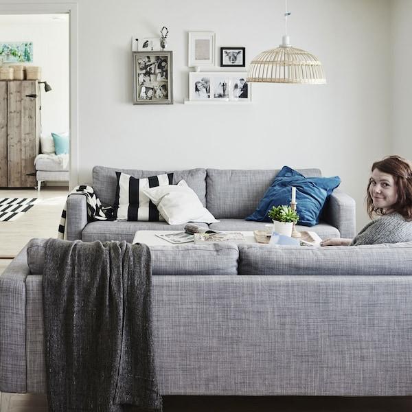 Un salón rústico con una mujer sentada en el sofá con mantas y cojines.