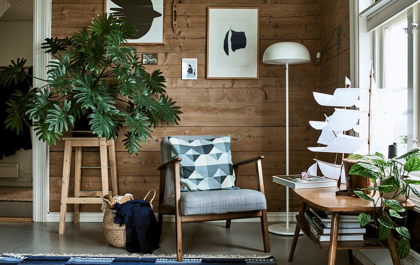 Un salon rustique avec un fauteuil à structure en bois, un lampadaire blanc et un tabouret faisant office de support pour une grosse plante feuillue.
