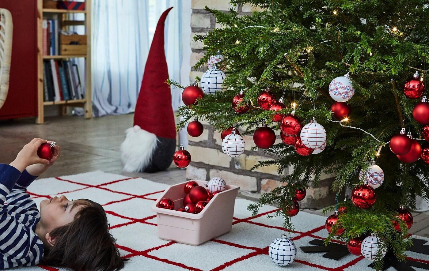 Un sapin de Noël chargé de décorations; un garçonnet couché sur le dos à côté, sur un tapis, en train d'examiner une décoration.