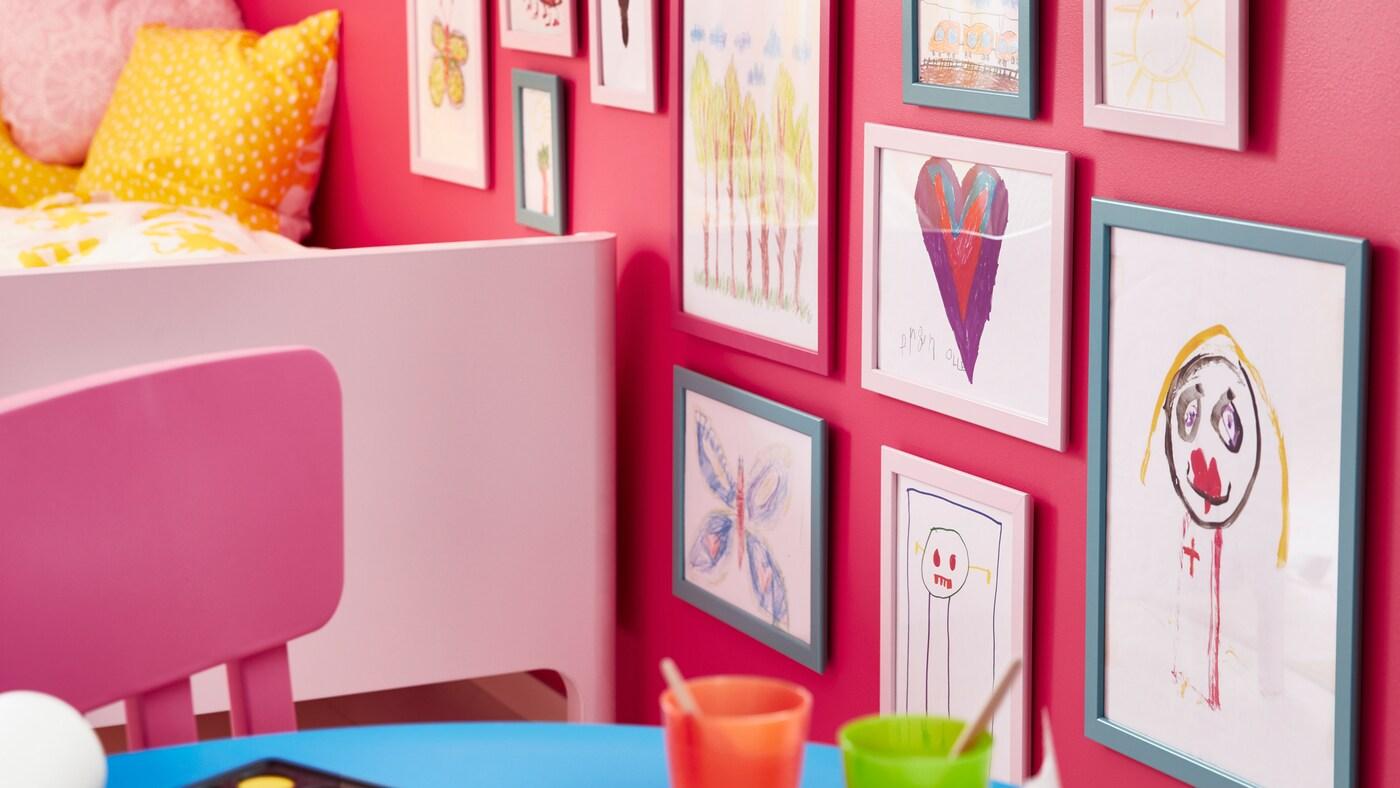 Un scaun pentru copii MAMMUT roz este așezat lângă un pat BUSUNGE și un perete acoperit cu rame FISKBO în care se pot vedea desene realizate de copii.