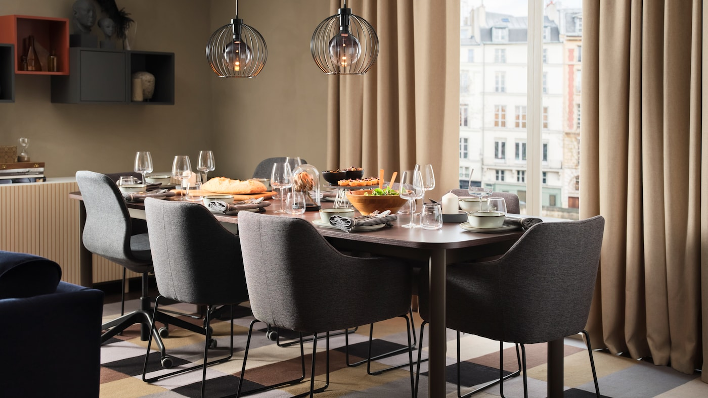 Un séjour beige avec une table extensible STRANDTORP dressée pour le dîner et entourée de chaises TOSSBERG et LÅNGFJÄLL.